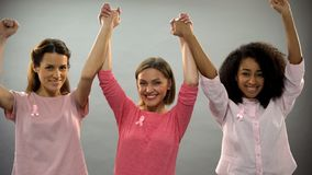 Smiling women with pink ribbon raising hands up, fighting against breast cancer. Stock photo stock photos