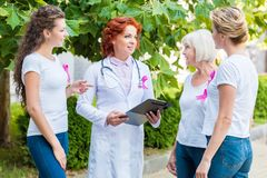 Smiling women with pink ribbons looking at doctor with clipboard breast cancer awareness. Concept stock photos