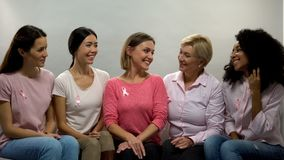 Smiling women with pink ribbons sharing experience, breast cancer awareness. Stock photo stock images