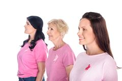 Women in pink t-shirts with ribbons. Smiling women in pink t-shirts with ribbons looking away isolated on white Royalty Free Stock Photo