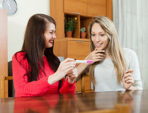 Smiling women with pregnancy test at table Stock Photography