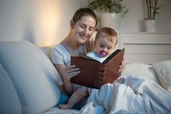 Beautiful smiling woman reading big old book to her baby boy before going to sleep. Smiling women reading big old book to her baby boy before going to sleep Stock Images