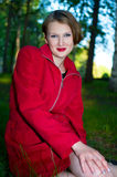 Smiling women in red raincoat Stock Photos