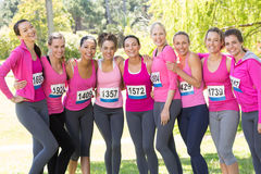 Smiling women running for breast cancer awareness. On a sunny day royalty free stock photo