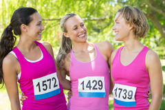 Smiling women running for breast cancer awareness. On a sunny day royalty free stock photography
