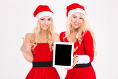 Smiling women in santa cloth showing tablet computer screen Royalty Free Stock Photos