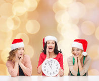 Smiling women in santa helper hat with clock. Christmas, winter, holidays, time and people concept - smiling women in santa helper hats with clock over beige stock image