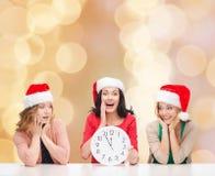 Smiling women in santa helper hat with clock Stock Image