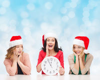 Smiling women in santa helper hat with clock. Christmas, winter, holidays, time and people concept - smiling women in santa helper hats with clock over blue stock photo