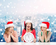Smiling women in santa helper hat with clock. Christmas, winter, holidays, time and people concept - smiling women in santa helper hats with clock over snowy stock photos