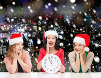 Smiling women in santa helper hat with clock. Christmas, winter, holidays, time and people concept - smiling women in santa helper hats with clock over snowy stock images