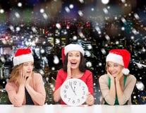 Smiling women in santa helper hat with clock Stock Images