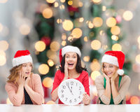 Smiling women in santa helper hat with clock. Winter, holidays, time and people concept - smiling women in santa helper hats with clock over christmas tree royalty free stock photography