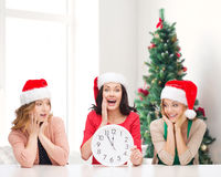 Smiling women in santa helper hat with clock. Winter, holidays, time and people concept - smiling women in santa helper hats with clock over living room and royalty free stock images