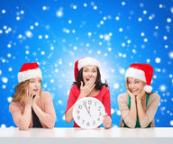 Smiling women in santa helper hats with clock. Christmas, winter, holidays, time and people concept - smiling women in santa helper hats with clock over blue stock photography