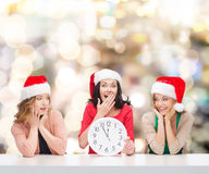 Smiling women in santa helper hats with clock. Christmas, winter, holidays, time and people concept - smiling women in santa helper hats with clock over lights royalty free stock photography