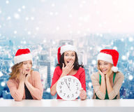 Smiling women in santa helper hats with clock Royalty Free Stock Photography