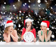 Smiling women in santa helper hats with clock. Christmas, winter, holidays, time and people concept - smiling women in santa helper hats with clock over snowy stock photo
