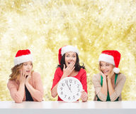 Smiling women in santa helper hats with clock. Christmas, winter, holidays, time and people concept - smiling women in santa helper hats with clock over yellow stock images