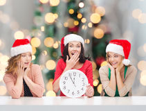 Smiling women in santa helper hats with clock. Winter, holidays, time and people concept - smiling women in santa helper hats with clock over christmas tree stock photography