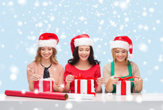 Smiling women in santa helper hats with gift boxes Royalty Free Stock Photos