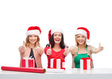 Smiling women in santa helper hats with gift boxes Royalty Free Stock Photo