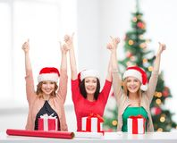 Smiling women in santa helper hats with gift boxes Stock Photography