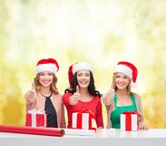 Smiling women in santa helper hats with gift boxes Stock Images