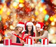 Smiling women in santa helper hats with gift boxes Royalty Free Stock Photography