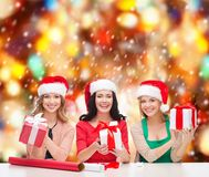 Smiling women in santa helper hats with gift boxes Royalty Free Stock Images
