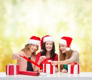 Smiling women in santa helper hats with gift boxes Stock Photos