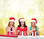 Smiling women in santa helper hats with gift boxes Royalty Free Stock Image