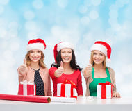 Smiling women in santa helper hats packing gifts Stock Photo