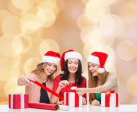 Smiling women in santa helper hats packing gifts Stock Images