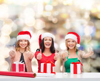 Smiling women in santa helper hats packing gifts Stock Photography