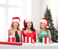 Smiling women in santa helper hats packing gifts Stock Photos