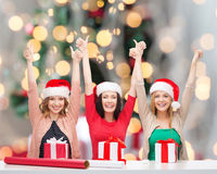 Smiling women in santa helper hats packing gifts Royalty Free Stock Images