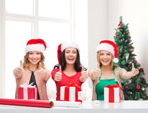 Smiling women in santa helper hats packing gifts Stock Image