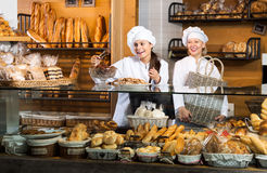Smiling women selling fresh pastry and loaves. In bread section. Focus on the young woman stock photography