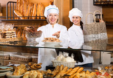 Smiling women selling fresh pastry and loaves. Cheerful women selling fresh pastry and loaves in bread section. Focus on the mature woman royalty free stock photos