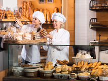 Smiling women selling fresh pastry and loaves. Pretty women selling fresh pastry and loaves in bread section and smiling stock image