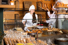 Smiling women selling fresh pastry and loaves. Two beautiful female seller fresh pastry and loaves of bread section and smiling stock photography