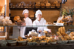 Smiling women selling fresh pastry and loaves. Two female seller fresh pastry and loaves of bread section stock photo
