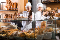 Smiling women selling fresh pastry and loaves. Two happy female seller fresh pastry and loaves of bread section royalty free stock photography