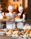 Smiling women selling fresh pastry and loaves. Two happy female seller fresh pastry and loaves of bread section and smiling stock photography