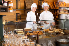 Smiling women selling fresh pastry and loaves. Two pretty female seller fresh pastry and loaves of bread section and smiling stock images
