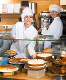 Smiling women selling tarts and sweet pastry Stock Images
