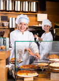 Smiling women selling tarts and sweet pastry Stock Photo