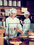 Smiling women selling tarts and sweet pastry Royalty Free Stock Photos