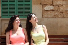 Smiling Women Sitting on a Bench Looking Up Stock Photography